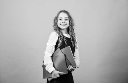 small girl with paper folder. hometwork. happy small girl wants to be teacher. Confident student studying