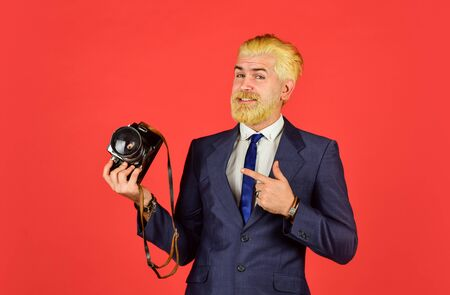 mature man dyed beard and hair. professional photographer make photo. male beauty. capture result of barbershop salon. vintage camera. confident businessman hold retro camera