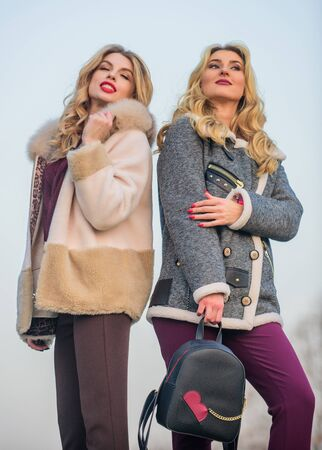 Girls enjoy cozy fancy chic coats. Natural wool sheepskin coats. Fur shop. Backpack fashion accessory. Stay warm and fashionable. Women wear furry coats. Winter clothes. Wardrobe for cold weather