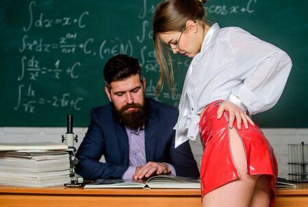 Versuchung zum Wissen. Bärtiger Mann und Studentin lesen Buch. Versuchung-Konzept. Sinnliche Frau mit verführerischen Hüften im roten Rock. In Versuchung führen. Verlangen und Versuchung