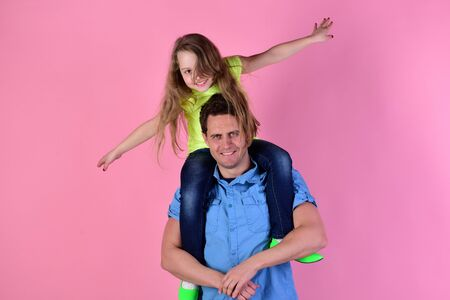 Daughter sits on dads shoulders. Schoolgirl puts hands wide Imagens