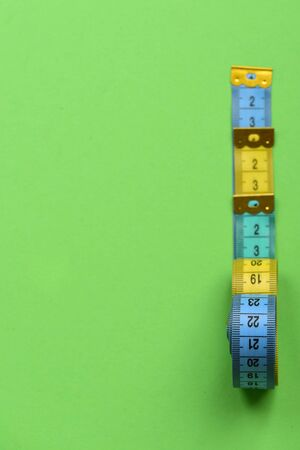 Creative measurements idea. Tape measures of cyan, blue and yellow colors placed in row. Fitness and measurement concept. Measuring tape rolls placed near each other on green background, top view