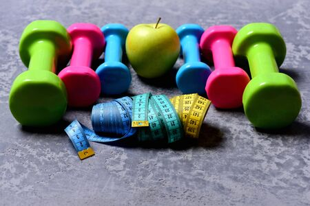 Barbells, tape measures and apple placed in pattern, close up