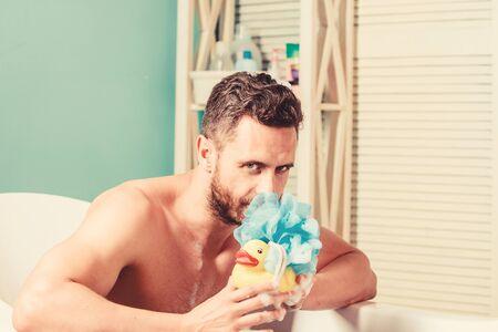 Macho naked in bathtub. funny duckling. playful mood. macho enjoy bath. Sexy man in bathroom. Sex and relaxation concept. man wash muscular body with foam sponge. Wash off foam with water carefully