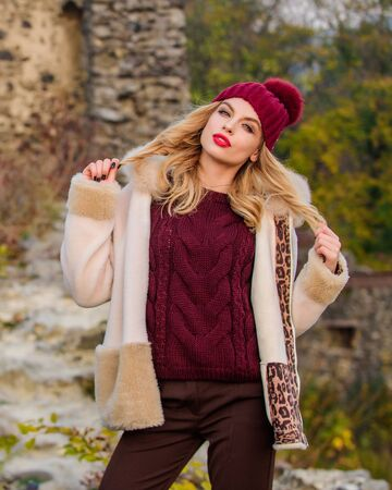 Quit morning. autumn season clothes and accessory. girl long hair in hat. woman in sweater and half-length coat. warm short faux fur coat in fall. sexy woman nature background. knitwear concept