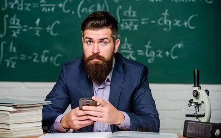 School application. Study technology. School teacher hold mobile phone chalkboard background. Teacher bearded man learn use modern technology. Learn technology. Modern communication. Send message
