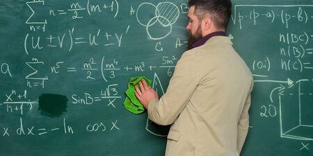 Bereiten Sie sich auf den Unterricht vor. Bärtiger Mann des Lehrers, der Tafelhintergrund säubert. Lehrer wischt Tafel ab. Schuldirektor. Anspruchsvolle Lehrerin. Dozent im Klassenzimmer. Theorie erklären. Lehrer halten Lappen Standard-Bild