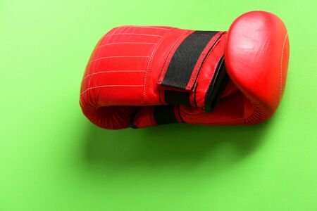 Training and fitness concept. Boxing gloves in red color. Pair of leather boxing sportswear. Sport equipment isolated on light green background.