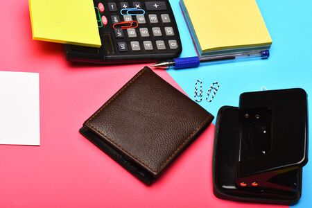Business and work concept. Calculator, hole punch, business card, note paper, pen and clips. Office tools isolated on pink and blue background, close up. Mans leather wallet and stationery.