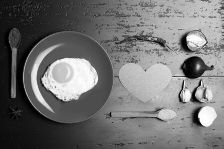 Dish with egg near spoons with spices, garlic, onion, eggshell, chili pepper and pink heart. Food placed on red plate on dark background. Omelet put in middle of plate. Breakfast and food art concept. Banco de Imagens
