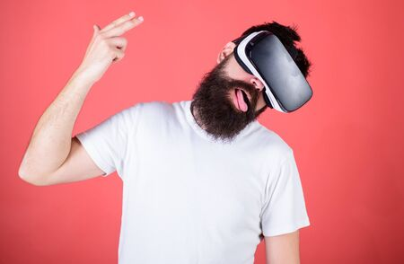 First person shooter shows how addictive VR could be. Suicide shot game. Man hand gesture as gun play shooter game in VR glasses. Man bearded hipster with virtual reality headset on red background
