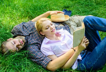 Romantic couple students enjoy leisure with poetry or literature grass background. Couple soulmates at romantic date. Couple in love spend leisure reading book. Man and girl lay on grass having fun