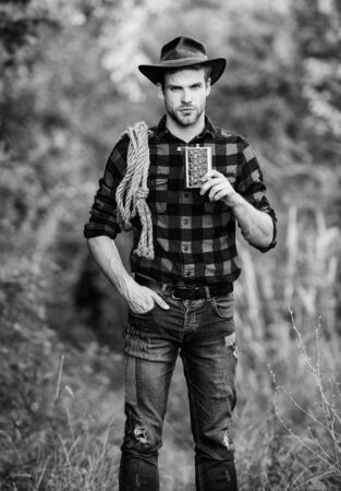 Cowboy ranch worker. Bourbon whiskey. Western culture. Man wearing hat hold rope and flask. Lasso tool American cowboy. Brutal cowboy drinking alcohol. Man handsome cowboy nature background 写真素材