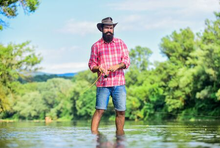 Some kind meditation. Fish normally caught in wild. Trout farm. Man bearded fisherman. Fisherman fishing equipment. Hobby sport activity. Calm and peaceful mood. Fisherman alone stand in river water