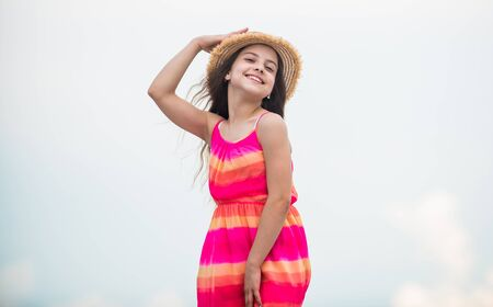 Happy vacation. Happy childhood. Enjoying relax. Child happy small girl. Free and carefree. Good vibes. Happy international childrens day. Cute girl in summer dress and hat outdoors sky background