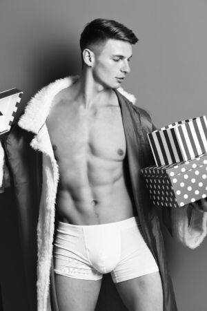 young handsome macho santa man with sexy muscular athletic strong body has, bare torso and strong belly in new year sweater holding christmas or xmas presents on red studio background Stock Photo