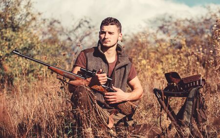 Man with rifle hunting equipment nature background. Prepare for hunting. What you should have while hunting nature environment. Recharge rifle concept. Hunting equipment and safety measures