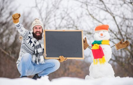 Winter holidays. Guy and snowman snowy nature background. Winter event. Upcoming event. Man with beard hold chalkboard copy space. Winter announcement. Hipster knitted hat and gloves show blackboard