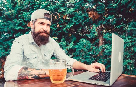 Laptop continues to assist virtual employees. Laptop user drinking beer in outdoor cafe. Bearded man working on laptop computer. Hipster using laptop with free internet access