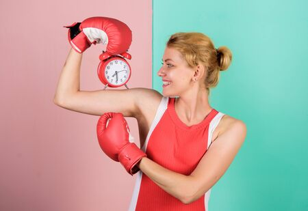 Control time. Punctuality and personal efficiency. Time management skills. Battle for self discipline. Woman holding clock boxing gloves. Boxer fighting with alarm clock. Time for boxing training