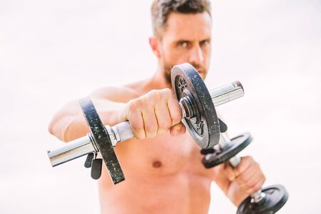 man sportsman weightlifting. athletic body. Dumbbell gym. success. Perfect biceps. Muscular man exercising in morning with barbell. fitness and sport equipment. Warming up for a workout routine