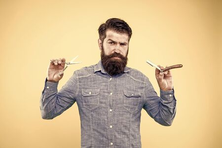 Retro barbershop. Hipster with old tools. Designing haircut. Fresh hairstyle. Barbershop concept. Care for men. Barbershop salon. Personal stylist. Vintage barber. Bearded man hold razor and scissors