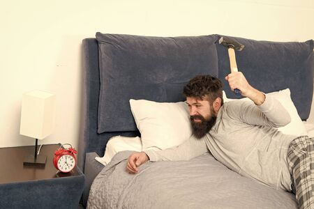 life routine. Healthy sleep concept. bearded man hipster want to sleep. hate noise of alarm clock. Irritated guy destroy annoying clock. Man awake unhappy with alarm clock ringing. Sleep longer Banco de Imagens