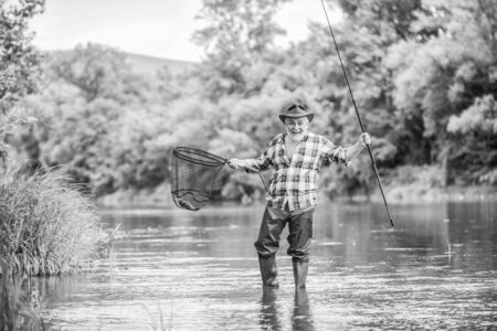 F for Fishing. hobby and sport activity. pothunter. fisherman with fishing rod. mature man fly fishing. man catching fish. retired bearded fisher. Trout bait. summer weekend. Big game fishing Banco de Imagens
