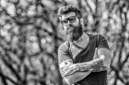 Man bearded with sunglasses nature background. Bearded hipster brutal man wear protective sunglasses. Hipster confident in dark sunglasses. Bearded man wear modern fashionable sunglasses. UV filter