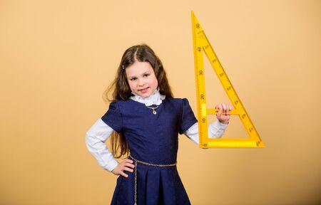 Kid in school uniform hold ruler