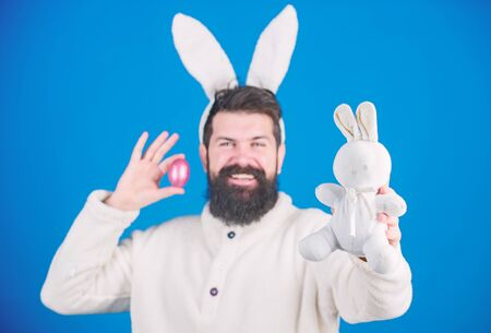 Being prolific. Easter bunny delivering colored eggs. Celebration of spring time holiday. Hipster with long rabbit ears holding egg laying hare. Bearded man with bunny toy and Easter egg