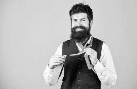 Do you like bearded men. Bearded man tying necktie. Cheerful man with unshaven bearded face and mustache hair dressing fashion accessory. Long bearded hipster adjusting neckwear, copy space Reklamní fotografie