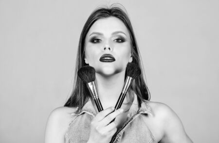 Skin care. Makeup cosmetics concept. Skin tone concealer. Cosmetics shop. Girl apply eye shadows. Woman applying makeup brush. Emphasize femininity. Different brushes. Professional makeup supplies