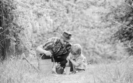园艺工具。德赢体育种植鲜花。爸爸教小儿子护理植物。在庭院里的小帮手。使行星更环保。种植植物。照顾植物。男孩和父亲本质上与喷壶