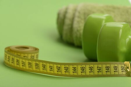Dumbbells in green color, twisted measure tape and towel on green background. Diet and sport regime concept. Tape measure in yellow color near lightweight barbells, close up. Healthy regime equipment Reklamní fotografie