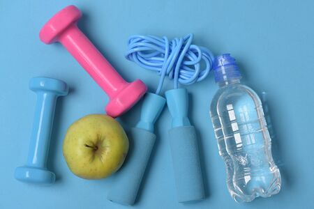 Jump rope, apple and barbells next to water bottle. Health regime and fitness symbols. Dumbbells and skipping rope in cyan and pink color on blue background, top view. Fit shape and sport concept Stock Photo