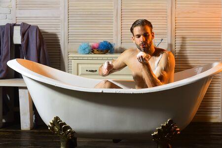 Macho spielt mit Schaum in der Badewanne. Kerl im Badezimmer