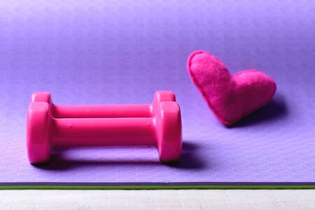 Dumbbells made of pink plastic near soft toy heart on purple texture background, selective focus. Healthy shape concept. Love of sports and fitness equipment. Barbells and pink love symbol, close up