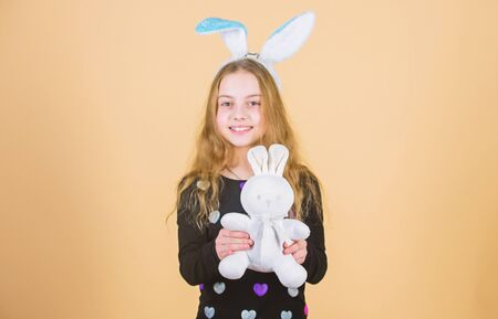 Hare is a symbol of fertility and spring. Small kid getting white hare gift on Easter day. Little girl holding Easter hare toy. Happy child playing with cute Easter hare