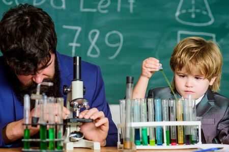 small boy with teacher man. Flask in scientist hand with Test tubes. Wisdom. Back to school. training room with blackboard. son and father at school. The best instructors educate from the heart.