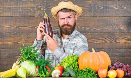 Farmer with organic vegetables. Excellent quality harvest. Grow organic crops. Organic fertilizers make soil and plants healthy and strong. Organic pest control. Man with beard wooden background