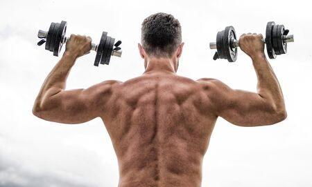 Pain is temporary, pride is forever. Sportsman with strong back and arms. Sport equipment. Bodybuilding sport. Dumbbell exercise gym. Muscular man exercising with dumbbell rear view. Sport lifestyle. Reklamní fotografie