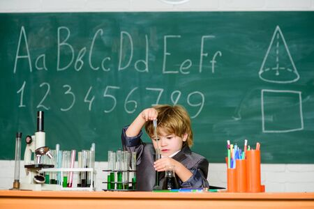 Boy near microscope and test tubes school classroom. Knowledge concept. Knowledge day. Basic knowledge primary school education. Kid study biology chemistry. Educational experiment. Happy childhood