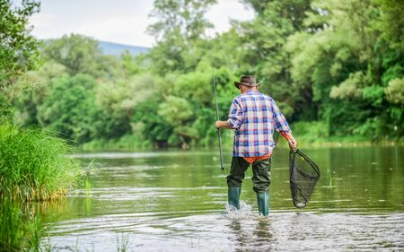 Calling Fly-Fishing a hobby. fisherman with fishing rod. retired bearded fisher. Trout bait. hobby and sport activity. mature man fly fishing. man catching fish. summer weekend. Big game fishing.
