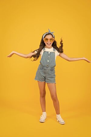 Summer fashion concept. Girl long curly hair wear sunglasses and fancy tied headscarf. Fashion trend. You can have anything you want in life if dress for it. Little fashionista. Cute kid fashion girl Stock fotó