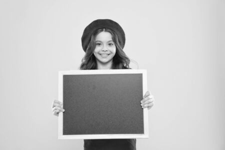 little girl kid with backboard, copy space. board for announcement advertisement. back to school. school shopping sales. kid fashion. happy school girl in parisian beret. We can Serve you better Archivio Fotografico
