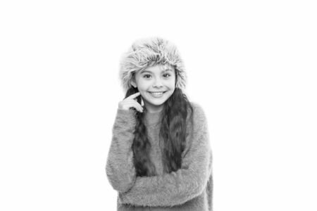 Charismatic kid girl wear hat with ear flaps white background. Soft furry accessory. Caring fur garments. Child long hair soft hat enjoy softness. Winter fashion concept. Warm hat for cold weather