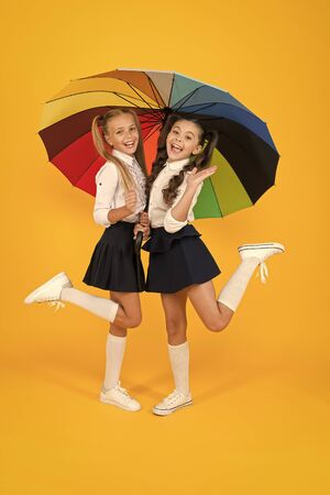 Primary school fashion. Happy school kids with fashion look holding colorful umbrella. Fashion small girls in formal uniforms smiling on yellow background. School fashion for little children Zdjęcie Seryjne