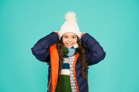 Cold season shopping. Child in padded warm coat. Seasonal fashion. Happy winter holidays. Fashion girl winter clothes. Fashion trend. Little kid wear hat and jacket blue background. Winter sports Foto de archivo