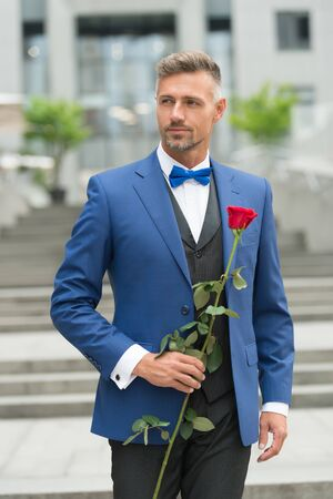 wedding preparation. valentines day concept. sexy man tuxedo and bow tie. be my wife forever. visit private party. elegant businessman presenting red rose. romance and love. day of his marriage Banque d'images